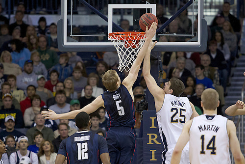 Notre Dame forward Tom Knight (#25) and Connecticut forward Niels Giffey (#5) battle on the glass in first half action of NCAA Men's basketball game between Connecticut and Notre Dame.  The Connecticut Huskies defeated the Notre Dame Fighting Irish 67-53 in game at Purcell Pavilion at the Joyce Center in South Bend, Indiana.