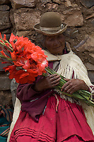 This old woman is selling flowes at the side of the road to Copacabana, on the Bolivian shore of Lake Titicaca. Every day, the owners of newly acquired vehicles drive them to Copacabana, park them in the town square, decorate them with flowers, garlands, dolls and other ornaments and wait for the priest to emerge from the Basilica de Copacabana to sprinkle them with holy water and bless them. Then firecrackers are set off and a good deal of alcohol is consumed before heading home.
