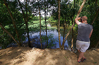 Phnom Penh, Cambodia. A pond at Choeung Ek Killing Fields memorial site, a reminder of the genocide committed by the Khmer Rouge.<br /> Tourist listening to the audio tour.