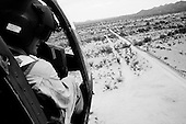 Cabeza Prieta National Wildlife Refuge<br /> Arizona<br /> USA<br /> August 24, 2007<br /> <br /> Army National Guard helicopter pilot Major George Harris flies over the Cabeza Prieta National Wildlife Refuge near the Mexican border. He searches for Mexican smugglers and illegal immigrants crossing into the US. He has more then a decade of experience flying this border. The National Guard can not arrest smugglers but can report them directly to the border patrol. Often too late. Of the 6,000 National Guard that began deployment in Arizona in 2006 on the US Mexican border, half remain.