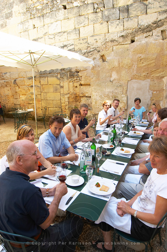 A group of wine and food tourists lunching outside in the restaurant L'Envers du Decor in Saint Emilion village  Saint Emilion Village  Bordeaux Gironde Aquitaine France