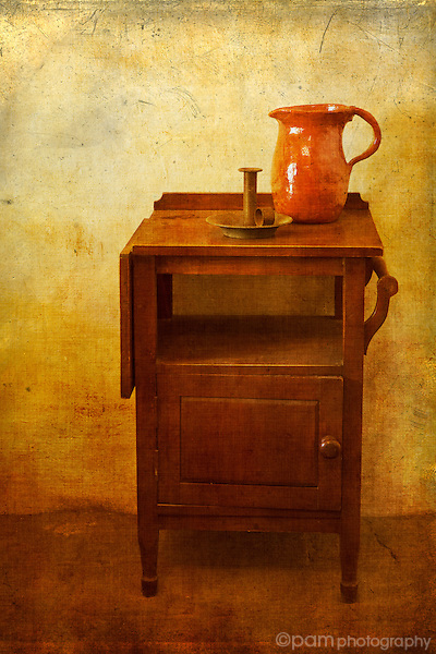Still life of pitcher and candlestick on nightstand.