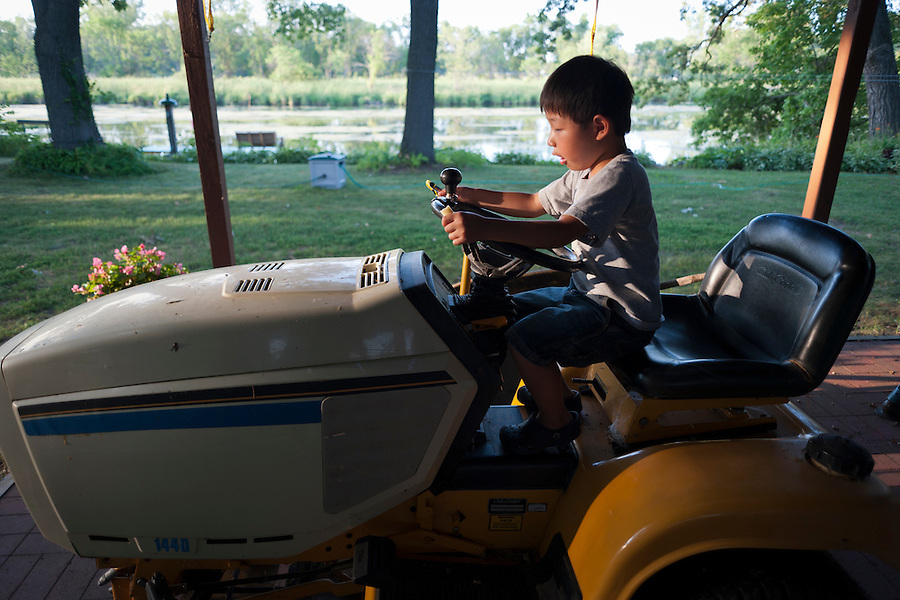 Done playing along the nearby Yahara River, Holden Miller, 5, pretends to drive a riding lawnmower at Trudy  Brule's home in McFarland, Wis., during summer on July 21, 2012.