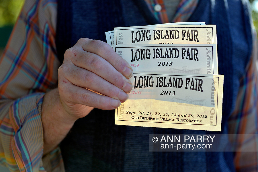 Old Bethpage, New York, U.S. 29th September 2013. Bob Stuhmer holds four Participant Pass admission tickets at The Long Island Fair. A yearly event since 1842, the county fair is now held at a reconstructed fairground at Old Bethpage Village Restoration.