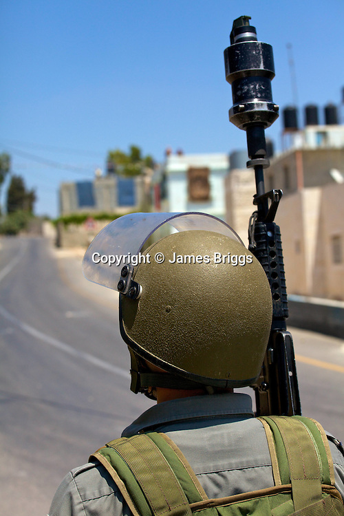An Israeli border police officer ready to fire a CS gas grenade at (unseen) Palestinian youths throwing rocks during protests against the expansion of the nearby Jewish settlement of Halamish, in the West Bank village of Nabi Saleh near Ramallah on 02/07/2010.