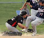 SIOUX FALLS, SD - JULY 1:  Jacob Mulder #12 from Valley Springs grabs the leg of Justin Kautz #17 from Sioux Falls Post 15 West, and attempts to put the tag on him in the fifth inning Monday night at Harmodon Park.  (Photo by Dave Eggen/Inertia)