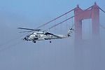 A U.S. Navy UH-60 Sea Hawk flies near one of the Golden Gate Bridge towers.