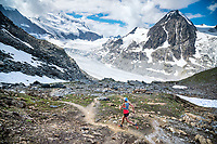 Trail running a loop from Fionnay, to Col des Ottans, to Cabane de Pannosiere and back to Fionnay, Val de Bagnes, Switzerland. Crossing the Col des Ottans and beginning the descent to Cabane de Pannosiere with views to Grand Combin.