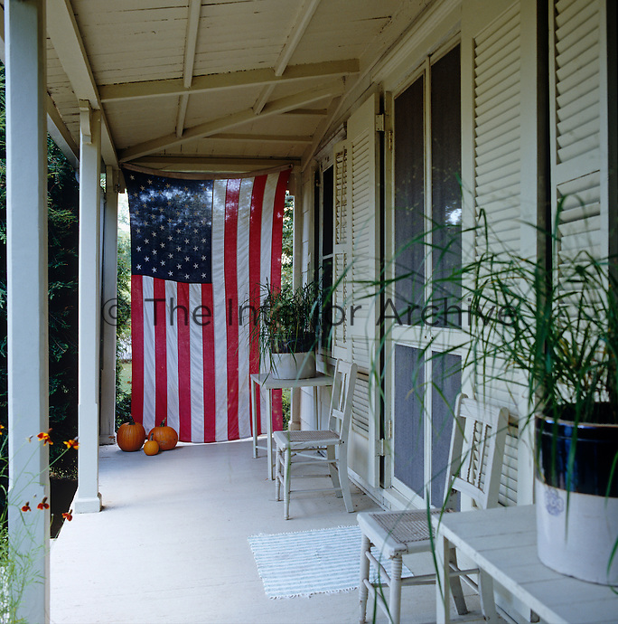 An American flag hangs at one end this porch, furnished with white painted chairs and tables