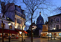 PARIS, FRANCE - JANUARY 20: A low angle view of Place du Tertre and Sacré-Coeur Basilica, on January 20, 2009, in Montmartre, Paris, France. The Sacré-Coeur Basilica, 1884-1914, designed by Paul Abadie, is seen through the deserted Place du Tertre in the blue light of an early morning in winter. Built in white travertine on the top of the Butte de Montmartre, the Romano-Byzantine style Sacré-Coeur was designed as a monument to those who died in the Paris Commune during the Franco-Prussian War, 1870-71. (Photo by Manuel Cohen)