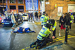 © Joel Goodman - 07973 332324 . 01/01/2016 . Manchester , UK . Police detain a man whilst another lies collapsed in the road . Revellers in Manchester on a New Year night out at the clubs around the city centre's Printworks venue . Photo credit : Joel Goodman