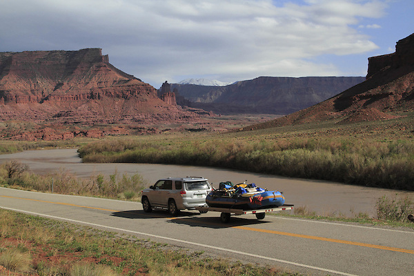 SUV pulling whitewater raft on Highway 128 along the Colorado River near Moab, Utah, USA.