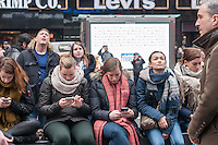 Millennials texting in Times Square in New York during the viewing of the inauguration of Donald Trump as the 45th president of the United States on ABC television's giant screen on Friday, January 20, 2017.   (© Richard B. Levine)