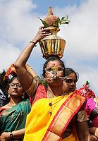 Nederland, Den Helder  2016  06 26. Jaarlijkse tempelfeest bij de Hindoe tempel in Den Helder.. Vereniging Sri Varatharaja Selvavinayagar voltooide in 2003 het gebouw dat wordt gebruikt voor het bevorderen van kunst en cultuur. Een ander deel wordt gebruikt voor het praktiseren van religieuze waarden. Het hoogtepunt van de feestperiode is het voorttrekken van de wagen ( chithira theer of ratham ). Dit is een kleurrijke optocht, waarbij de godheid Ganesh in de wagen wordt voortgetrokken door gelovigen. Vrouwen dragen kokosmelk en kokosnoten.  Bij de vrouw op de voorgrond is een pijl door de mondhoeken gespiest.  Foto Berlinda van Dam /  Hollandse Hoogte