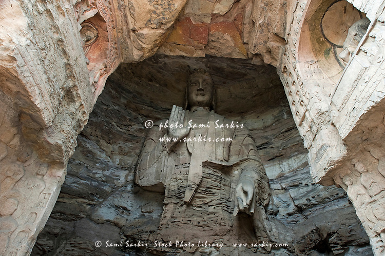Damaged Buddha statue carved inside the ancient Yungang Grottoes, Datong, Shanxi, China.