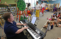 NWA Democrat-Gazette/DAVID GOTTSCHALK Andrew Voelker, pianist with the Studio Artists of Opera in the Ozarks, plays Thursday, July 11, 2019, during the children's opera Monkey See, Monkey Do at the Springdale Library. Children in the audience received an opera related activity book. The artists will perform at the Bentonville Public Library on Saturday, July 13th at 2:00 p.m..