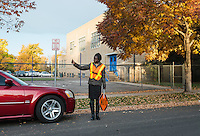 Mary Kuanen working as a crossing guard at Blessed Sacrament Catholic School in Denver, Colorado, Friday, October 21, 2016. Kuanen a refugee from Sudan moved to Denver 11 years ago with her husband and children. Five years ago her husband was murdered in a mistaken identity gang shooting. <br /> <br /> Photo by Matt Nager