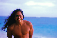 Young Hawaiian man at sunrise on the beach, Oahu