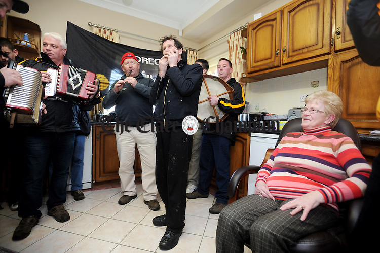 Mary Meaney looks on as the wrenboys from Coolmeen GAA Club perform in her kitchen in Cranny on St Stephen's Day. Photograph by Declan Monaghan