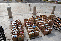 Bags of food and supplies are lined up on the street outside Town Hall for distribution to families in need by the Belmont Food Pantry in Belmont, Massachusetts, on Sat., March 21, 2020. As part of the response to the ongoing Coronavirus (COVID-19) global pandemic, the Belmont Food Pantry arranged for curbside pickup to minimize person-to-person contact. Each pair of bags included a variety of nonperishable food, including some canned meats, and toilet paper and paper towels. The Food Pantry usually purchases food directly from grocers and food providers for distribution, but because of ongoing shortages, the Food Pantry received donations from the Greater Boston Food Bank in order to keep up with ongoing food distribution.