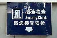 Daytime landscape view of security check signage on a wall at a B?ij?ng dìti?zhàn in D?ngchéng Q? in Beijing.  © LAN