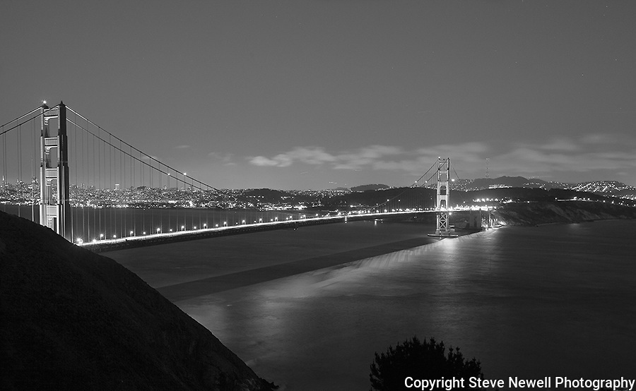 """The Night Life"" Black and White. Golden Gate Bridge San Francisco, California. I have printed it as large as 48x84""s with it being hung in Board Rooms.  It is unusual for a night shot in a large print format to have such sharp detail of the Golden Gate Bridge and the City.  A few of the things I like in this photograph and in my opinion make it a ""One of a Kind"" are: the colors of the bridge, the shadows of the cables on the Pacific Ocean, looking at the ocean you can see how the waves are moving in several different directions (something not readily visible during the day), white clouds being illuminated by the city lights and are slightly blurry showing that they were moving, the detail of all the buildings and their light in the windows, the Trans America building on the left, the Presidio on the right, the little slivers of light in the sky are airplanes in flight, stars in the sky high above the city and the cars driving over the bridge look like a laser beam of light but when you look closely you can see little bubbles of light sticking out above the main stream of light due to the cars bouncing on the suspension bridge.  I didn't realize how much the vehicles bounced until I viewed their light trails while going over the bridge. I have four different images of this scene with some of them having the vehicle light trails only being little individual lines of light that look like little snakes.  I get asked a lot about the camera settings I used to capture this image so here they are: Picture taken on June 24th, 2012 at 9:32pm, ISO 400, 30 second exposure, f13.0 aperture, with a Canon 5D Mark ll and Canon F/2.8 L series lens set at 35mm."