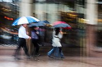Group of downtown office works navigate through the rain in downtown Austin, Texas, motion blurred.