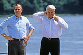 President Boris Yeltsin of the Russian Federation, right, adjusts his collar after removing his tie as he and United States President George H.W. Bush, left, take a boat ride on the Severn River in Maryland on June 17, 1992. <br />