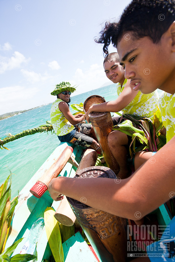 Young Tahitian men pkaying drums at finish line of yacht race