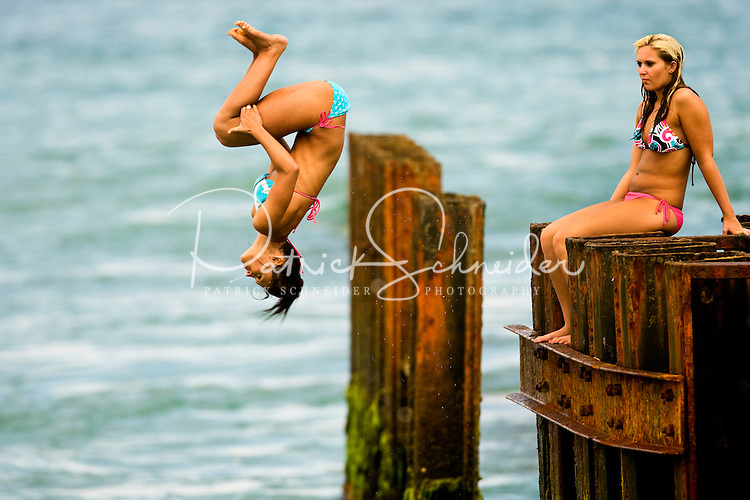 A beach goer makes a back flip into the ocean from a sea wall along Cape Hatteras Beach, near the Cape Hatteras Lighthouse. The Cape Hatteras Light house is one of the most recognized American lighthouses and a famous symbol of North Carolina. Cape Hatteras is one of the few North Carolina lighthouses where visitors can climb the inside stairs to the top. Cape Hatteras has white and black spiral bands and a red brick base. The lighthouse's beacon of light can be seen some 20-miles out to sea and has warned sailors for more than 100 years about the treacherous Diamond Shoals, the shallow sandbars which extend some 14 miles out into the ocean off Cape Hatteras. Charlotte NC photographer Patrick Schneider has extensive photo collections of the following lighthouses: Bodie Island Lighthouse, Bald Head Island Lighthouse, Cape Fear Lighthouse, Cape Hatteras Lighthouse, Cape Lookout Lighthouse, Currituck Beach Lighthouse, Diamond Shoal Lighthouse, Federal Point Lighthouse, Oak Island Lighthouse, and Ocracoke Lighthouse on Ocracoke Island.