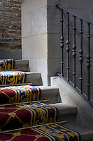 A detail of a red pattern carpet with brass stair-rods on stone steps in the Parador hotel, Hostal dos Reis Catolicos