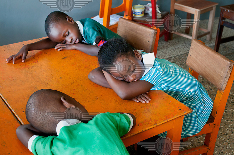 School children sleep at their desks at the North Ridge Model Kindergarden.