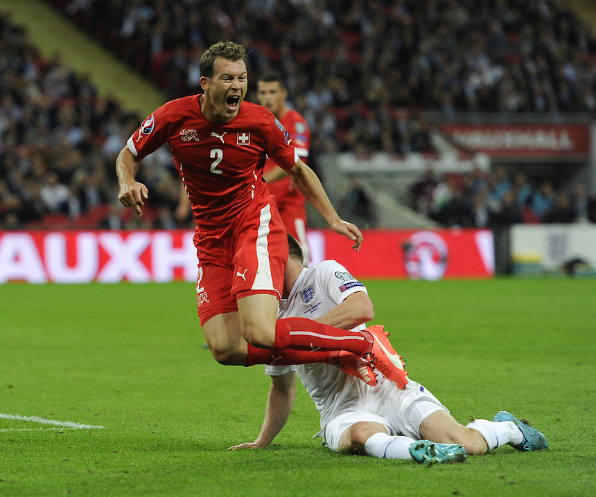 Switzerland&rsquo;s Stephan Lichtsteiner is fouled by England&rsquo;s James Milner <br /> <br /> Photographer Ashley Western/CameraSport<br /> <br /> International Football - UEFA EURO 2016 - UEFA European Championship Qualifying Group E - England v Switzerland - Tuesday 8th September 2015 - Wembley Stadium - London<br /> <br /> &copy; CameraSport - 43 Linden Ave. Countesthorpe. Leicester. England. LE8 5PG - Tel: +44 (0) 116 277 4147 - admin@camerasport.com - www.camerasport.com