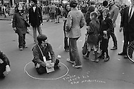 "22 Apr 1970 --- Pedestrians walk past a demonstrator who is sitting in the middle of the street inside a chalk circle with the message ""Please don't hit the pedestrian"" pointing at him. Various public demonstrations and rallies are taking place around New York City during the first Earth Day. --- Image by © JP Laffont"