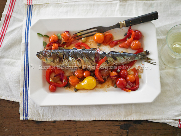 A grilled whole sardine with sauteed peppers and cherry tomatoes
