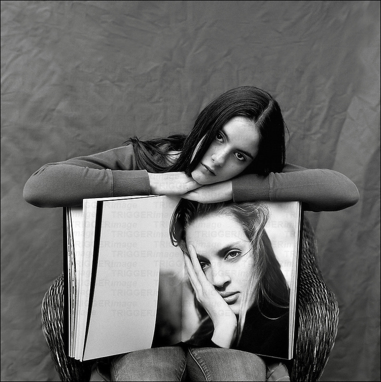 A young woman leaning on the edge of a large book