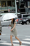 July 8, 2011 - Tokyo, Japan - A walking holding a fashionable parasol walks across the street in Ginza's shopping district. Japanese people, especially middled-aged women, use parasols during the hot Summer months to avoid any form of skin cancer. Today, parasols are also becoming popular among young adult women due to various designs and colors available on the market. (Photo by Yumeto Yamazaki/AFLO)