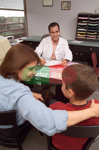 mother talking to 12 year old son during consultation while doctor looks on
