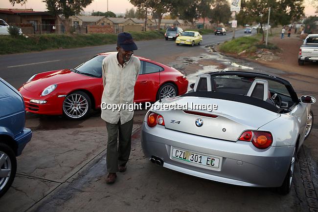 A Sowetan walks by a BMW convertible and a Porsche at a car wash in soweto.