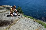 Young boy resting on Monhegan Island's rugged Eastern shore, Monhegan Plantation, Maine, USA
