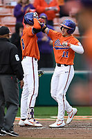 Right fielder Michael Green (11) of the Clemson Tigers is greeted by Logan Davidson after hitting a home run in a game against the South Alabama Jaguars on Opening Day, Friday, February 15, 2019, at Doug Kingsmore Stadium in Clemson, South Carolina. Clemson won, 6-2. (Tom Priddy/Four Seam Images)