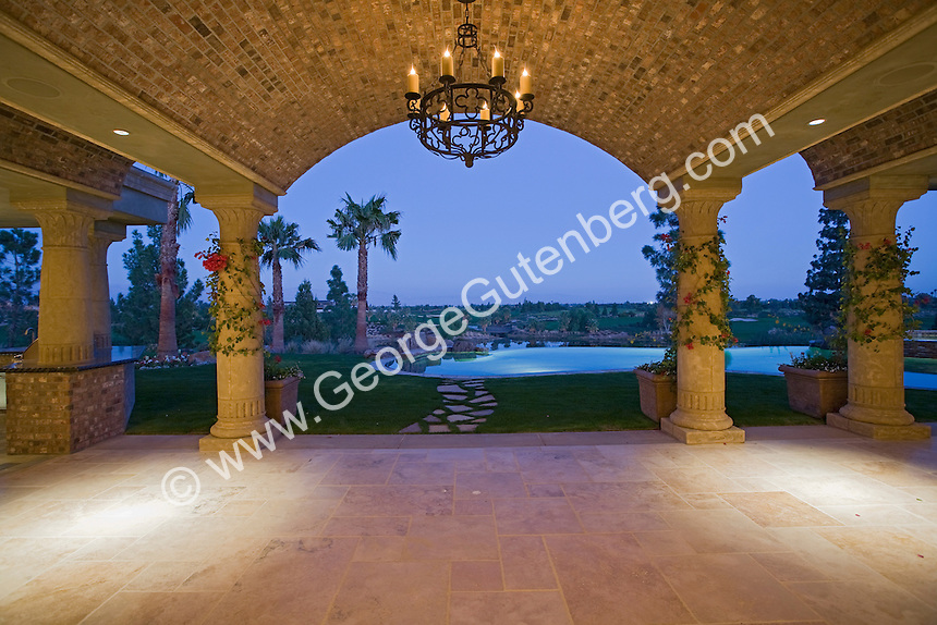 Outdoor covered patio with fireplace is seen with open pocket doors to inside