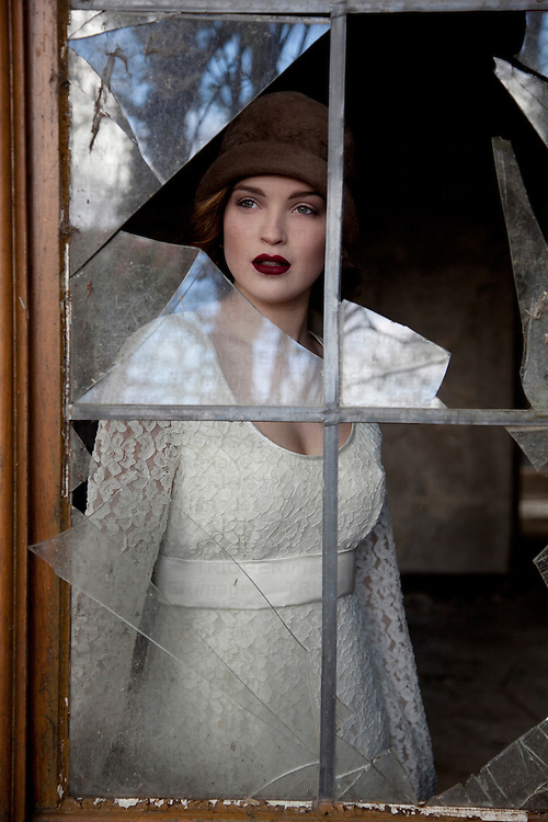 woman standing infront of a broken window