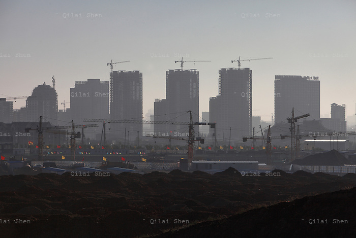"""A view of densely built residential apartment developments near the Kangbashi New District of Ordos City, Inner Mongolia, China on 16 August, 2011. With an investment of over 161billion USD from the local government and revenue from the region's rich coal deposits, enough buildings have risen on the site of an old desert village to hold at least 300,000 residents, complete with ultra modern facilities and grand plazas. The district however is less than 10% occupied, dubbed the """"ghost city"""", Kangbashi epitomizes China's real estate bubble and dangers in mindless investment fueled economic  growth. In 2011, the real estate price of Ordos city has dropped over 70%."""