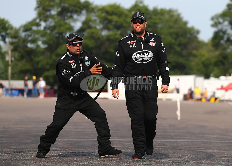 Aug. 18, 2013; Brainerd, MN, USA: NHRA top fuel dragster driver Khalid Albalooshi (left) jokes with teammate Shawn Langdon during the Lucas Oil Nationals at Brainerd International Raceway. Mandatory Credit: Mark J. Rebilas-