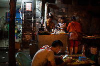 Neighborhood locals eat at a nameless shaokao barbecue restaurant on the sidewalk near the west gate of the Ciqikou area of Shapingba district in Chongqing, China. The pair, who said they live nearby, said they were eating mostly chicken meat and chicken skin. &quot;This is the best shaokao,&quot; they said, explaining why there were eating at the restaurant this evening, &quot;The flavor is the best.&quot; Ciqikou's ancient town is a major tourist destination in Chongqing, but at night, the tourists disappear and locals come out to eat from street food vendors in the area.<br /> <br /> The restaurant is run by Liu Pang Wa, whose wife and two children also help. Most of the customers there are neighborhood locals, and the restaurant stays open until 3 or 4 am. Liu Pang Wa said his specialties are eggplant, pig brain, and fish. The area is close to western banks of the Jialing River in northwestern Chongqing city.