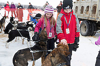 Young Aiden and Kara Hollingsworth pet Iditarod sled dogs in the staging area at the restart of the Iditarod sled dog race in Willow, Alaska Sunday, March 3, 2013.