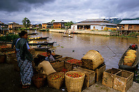 Woman unloading wicker baskets full of tomatoes along a riverbank.