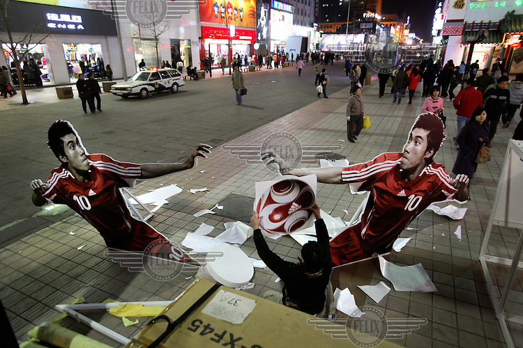 A man mounting an Adidas stand featuring a Chinese football star who will represent China during the 2008 Olympic Games..
