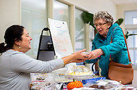 NWA Democrat-Gazette/JASON IVESTER <br /> Ginger Nelson (right) of Rogers purchases a pumpkin pie from Sahara Hoskins, Rogers Adult Wellness Center administrative assistant, on Wednesday, Nov. 25, 2015, at the center. Members and staff baked goods for the Holiday Pie &amp; Goodie Sale which raises funds for the center.